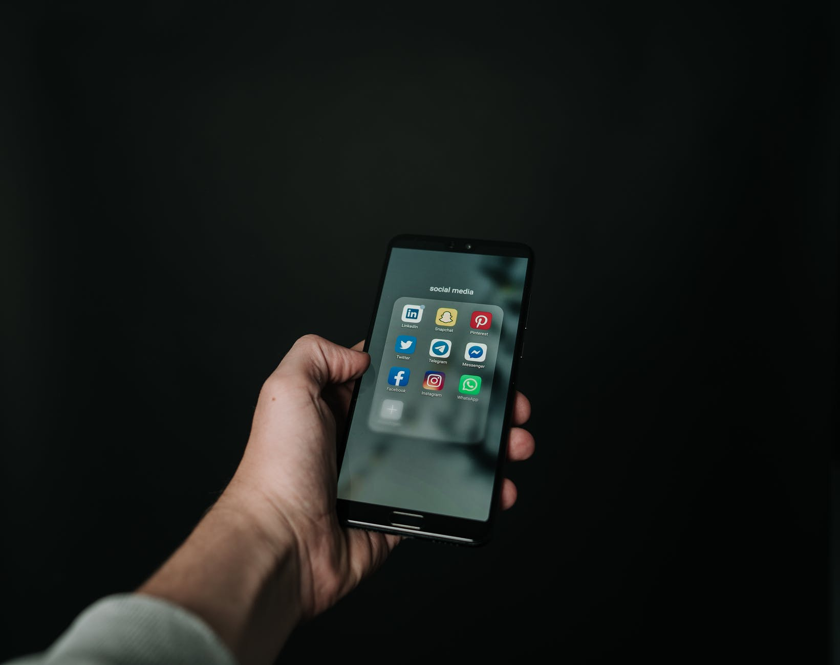 photo of hand holding a black smartphone