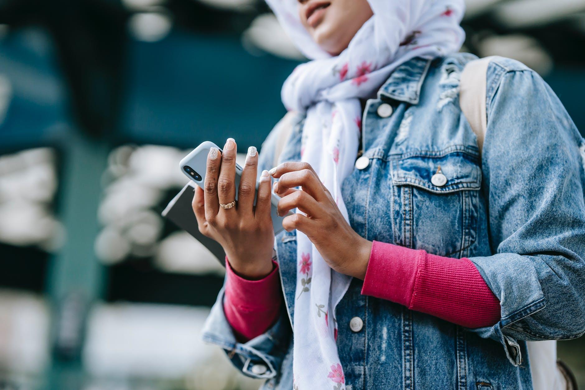 crop ethnic woman surfing smartphone in city street