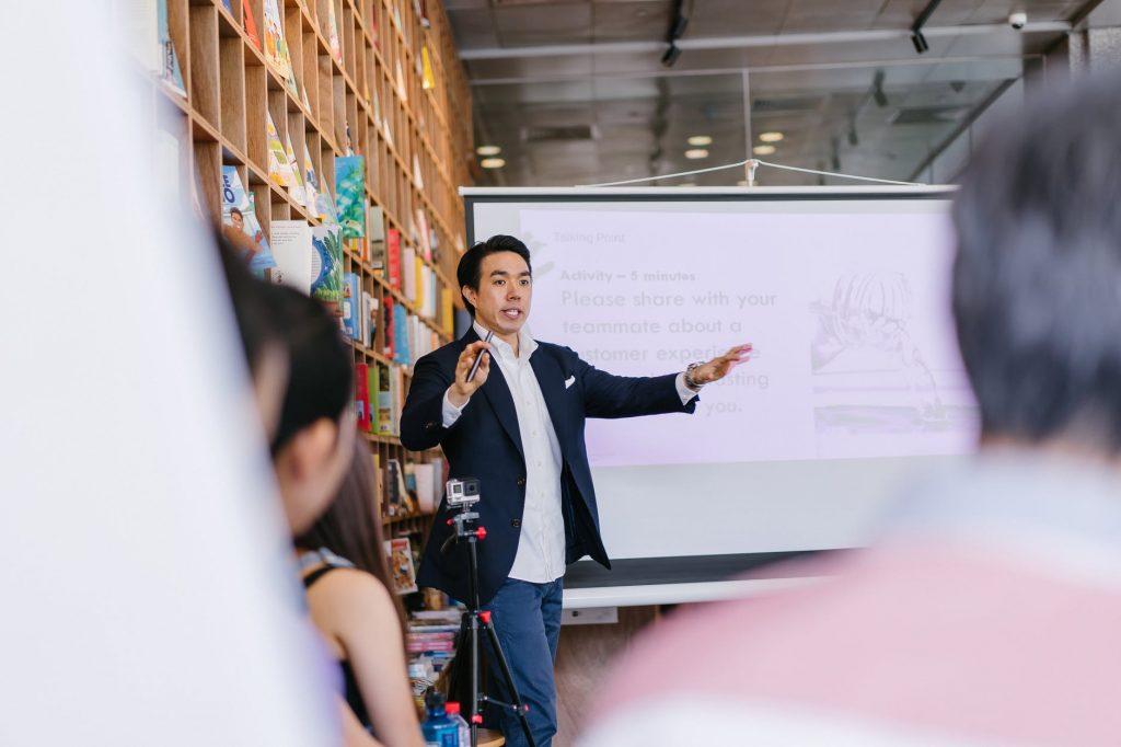 man in suit jacket standing beside projector screen